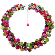 Bright multicolored choker necklace made of gemstones. Crimson, green, fuchsia, beige, brown,