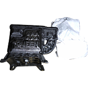 Miniature cast iron coal stove. On the front door , it says Queen