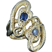 A stunning two snakes crossover ring with sapphire and diamond