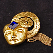 Art deco brass fur clip with diamond blue glass jewel on a stylized mask with dangling chains