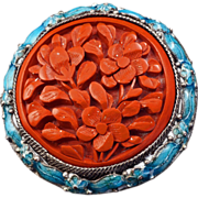 Chinese cinnabar circular pin edged with an enamel wreath backed with silver circa 1900
