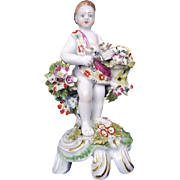 An English Bow Porcelain Figure Of A Putti Holding Basket With Flowers Standing On A Prong Scroll, Marked c.1760