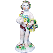 An English Bow Porcelain Figure Of A Putti Holding A Basket, c.1760