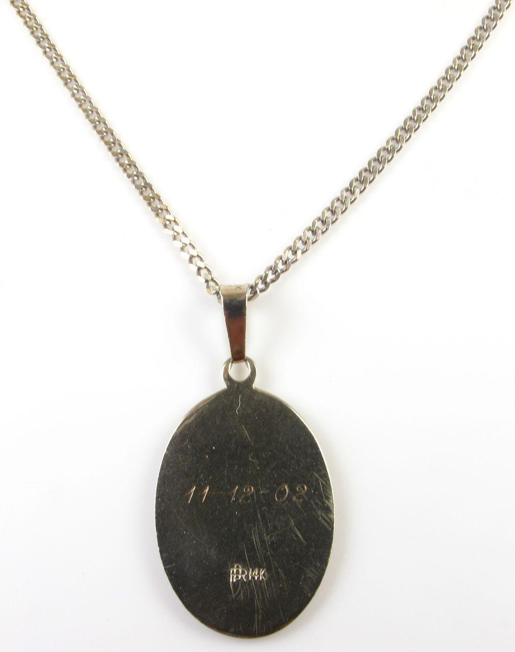 vintage 14k white gold christopher pendant on curb