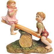 Whimsical Lefton Bisque Girl and Boy on Seesaw Figurine