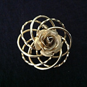 Gold tone rose in setting of off-set circles