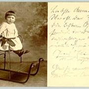 1909: Little Girl in a Toboggan. Old Austrian Postcard