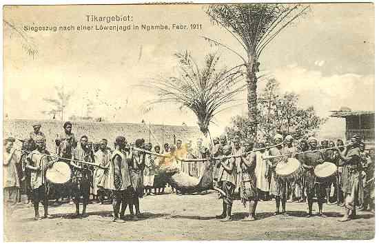 1911: Lion Hunting: African Hunters celebrating after the Hunt. Nintage Postcard.