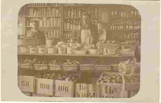 1909: Photo of an old Grocery Shop as Postcard