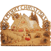 Cottage & Victorian couple under a Merry Christmas banner cardboard Christmas Decoration made in Germany