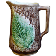 Beautiful large America majolica leaf and fern pattern pitcher on a brown bark background