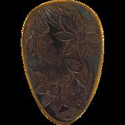 Deeply carved floral dark green Bakelite dress clip
