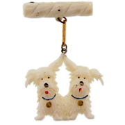 Early plastic figural brooch of two white scottie dogs