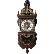 Wooden hanging clock with ornate and figural hardware