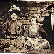 RPPC Real Photo Postcard Mother Father Daughter In Their Sunday Best Sitting Against Stone Wal