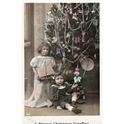 Tinted Photo of Two Children at a Christmas Tree Vintage Christmas Postcard