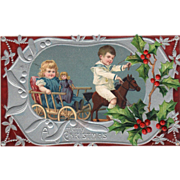 Two Children Playing with a Toy Horse and Wagon Vintage Christmas Postcard