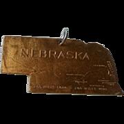Brass Nebraska fob.  Die cut shape of the state. Whitehead and Hoag