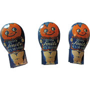 "Three Cute ""Drink Smile"" Advertising Tin Toy Clickers"