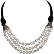 Three strands white pearls black leather choker silver clasps