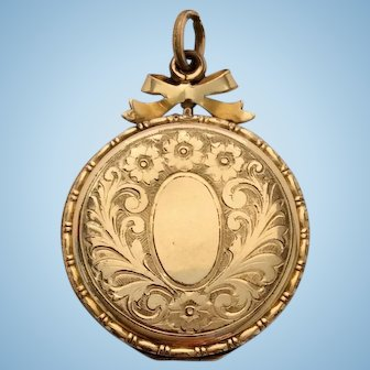Antique rolled gold locket with pretty bow top decoration