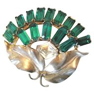 Sterling flower pin made with rectangular green rhinestones and a paste accent with sterling leaves