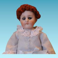 """German Antique all bisque doll with Hairline on mold line,  caracul red wig and baby blue dress. Reglue on one lower leg all the way around. Incised #540, 6 1/4"""" tall."""