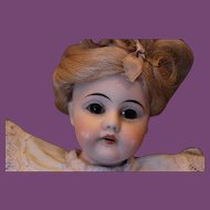 """11 1/2"""" tall unmarked German antique doll, possible Kestner doll. She has long blond wig, new blue rayon dress, blue socks, plastic shoes. Cheek blemishes."""