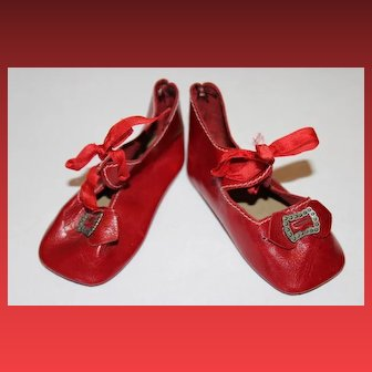 """Red leather doll shoes in great condition. Buckles intact. Measures 3 3/8"""" long X 1 1/2"""" wide in size. Marked 9 or 6 on the bottom of the shoes."""