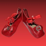 "Red leather doll shoes in great condition. Buckles intact. Measures 3 3/8"" long X 1 1/2"" wide in size. Marked 9 or 6 on the bottom of the shoes."