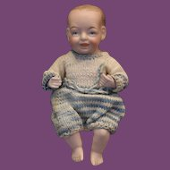 """Adorable antique all bisque baby boy, unknown maker, marked 230, 14. almost 6"""" long in size, can sit, needs restringing on legs. replaced legs and arms. Painted features. I cannot make out the number on the arms."""