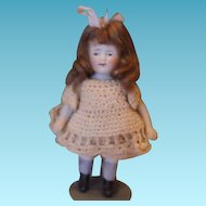 "Cute little 4 1/2"" tall all bisque girl doll with  nice brown mohair wig, cute beige crochet dress and pantaloons, unmarked. closed mouth doll."