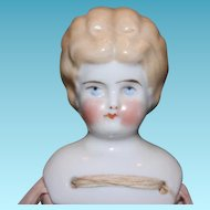 "11"" tall blond china head with replaced cotton body. Crude bisque arms and legs. No clothes."