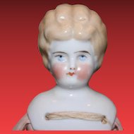 """11"""" tall blond china head with replaced cotton body. Crude bisque arms and legs. No clothes."""