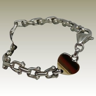 Sterling Silver Fancy Link Bracelet with an 18k Yellow Gold Heart Accent.