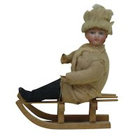 Early Bisque head sledder cotton Christmas ornament
