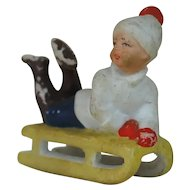 1920's German Snow Baby Figure on Yellow Sled