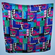 A Large Scarf With A  Busy Pattern Featuring  Flowers Diamonds Stripes And Much More
