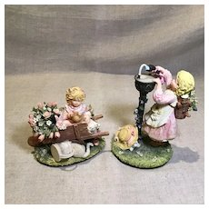 Two Molded Figurines of Girls and Dolls