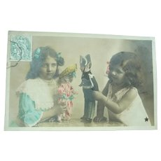 Vintage French postcard of two girls Playing wiyth Their Dolls