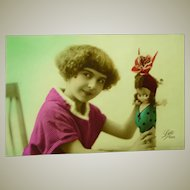 Early 1900's Photo Postcard of a Girl and her Kewpie Doll