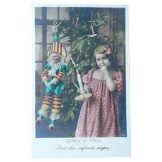 Wonderful Real Photo Postcard of a Little girl and her Jester Doll at Christmas