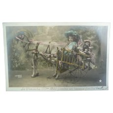 Vintage Real Photo French Postcard of a Child and her Dolls in a Cart