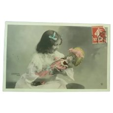 Vintage Real Photo French Edwardian Postcard of a girl cradling her doll