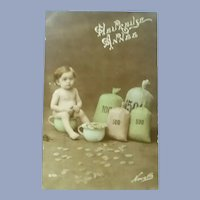 Vintage French Real Photo Postcard of a Baby with bags of Money