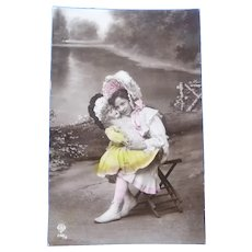Vintage French Real Photo Postcard of a Girl and her Prized Doll