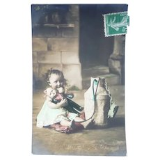 Vintage Real Photo Postcard of a girl and her doll
