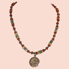 Tibetan Coin pendant reproduced in guild bronze and hung  on a  multi gemstone necklace