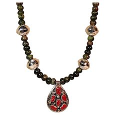 Signed Rhoda Jack Navajo pendant set with blood coral cabochons and strung on leather cord with Nephrite Jade beads.