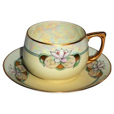 Hand painted porcelain teacup and saucer from the early 20th century